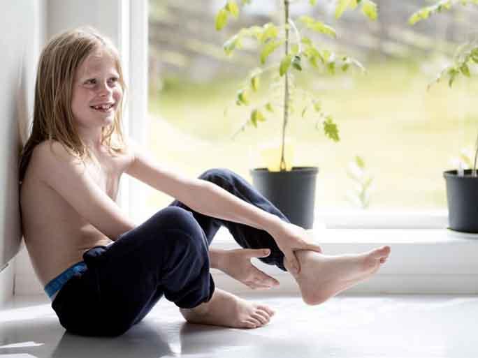 Jente sitter på gulvet. Foto